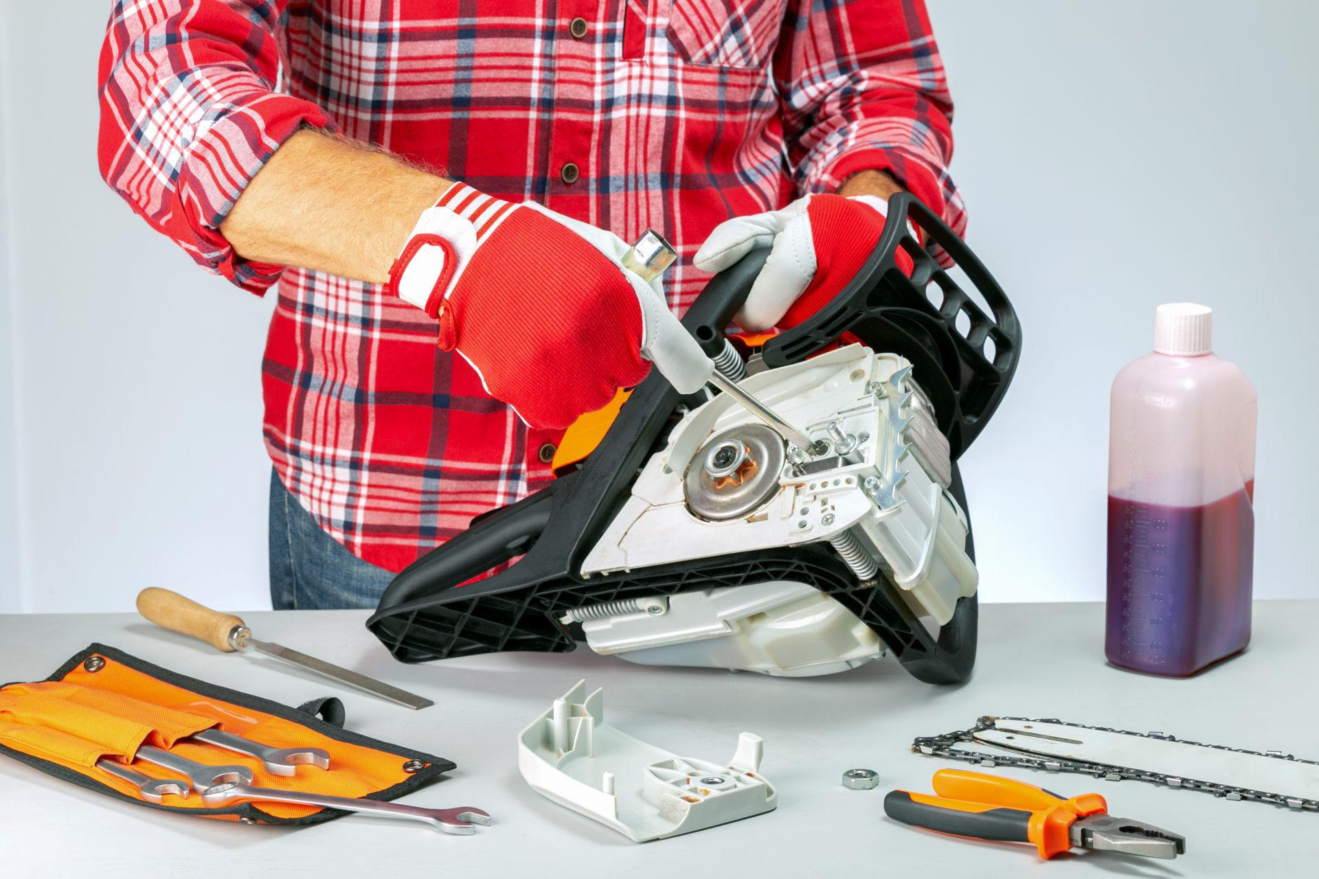 Serviceman,Is,Repairing,A,Chainsaw,In,Repair,Shop.,Repair,And
